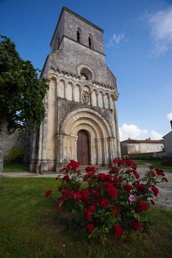 Facade of the romanesque Rioux church with red  roses in the forefront. Region of Charente in France