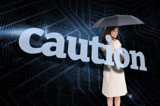 Businesswoman holding umbrella behind the word caution