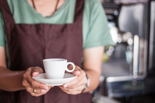 Asian barista serving freshly brewed coffee