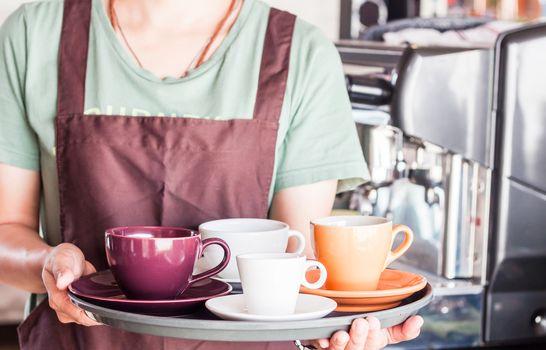 Barista preparing set of freshly brewed coffee for serving