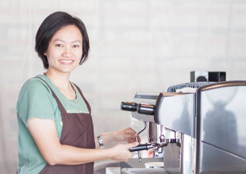 Asian barista smiling and making cup of coffee, stock photo