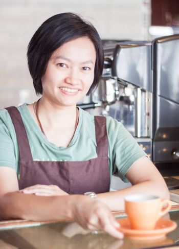 Smiling asian barista   posing with cup of coffee, stock photo