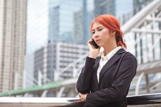 Young business asian woman calling on the phone at modern city