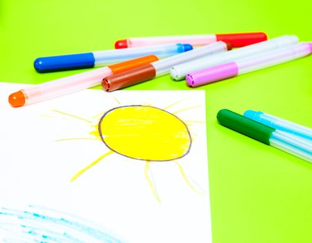 Childs drawing of sun and color pens