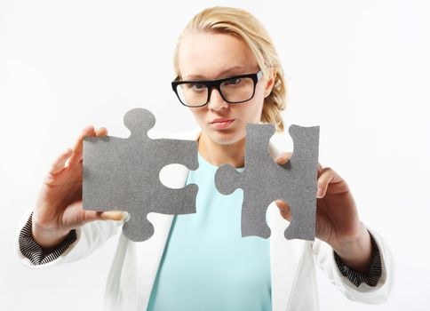 Attractive woman in business outfit adjusts the pieces of the puzzle