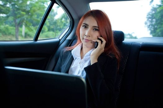 Beautiful young business asian woman using laptop and mobile phone in a car