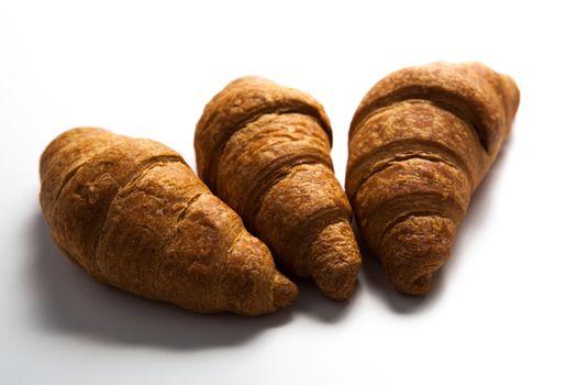 three croissant on grey