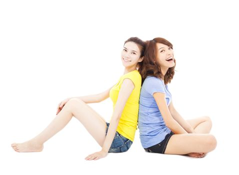 two smiling  young woman sitting and back to back
