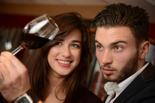 Young couples with redwine glasses at celebration or party