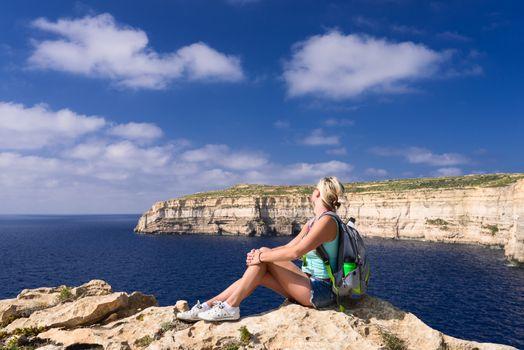 Woman looking at coastline near Azure Window on Gozo Island