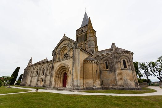 Side, abse and tower views of Aulnay de Saintonge church in Charente Maritime region of France
