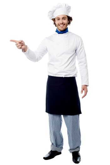Young male chef pointing to a product