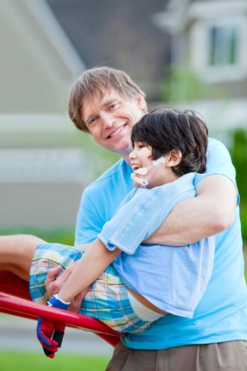 Father helping disabled seven year old son play at playground