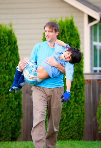 Father carrying disabled son outdoors