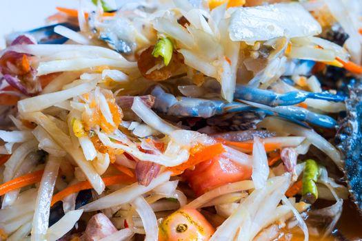 Thai popular dishes, spicy papaya salad with raw blue crab
