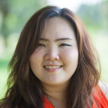 Close up of happy fatty asian woman outdoor in a park