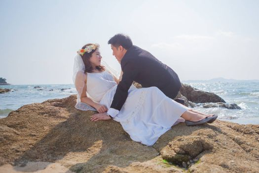 Happy young asian couple in love outdoor on the beach