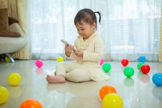 Happy little asian girl using mobile phone in the home