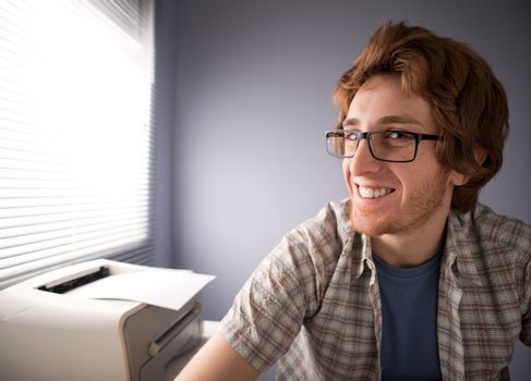 Funny nerd guy with glasses smiling, office on background.