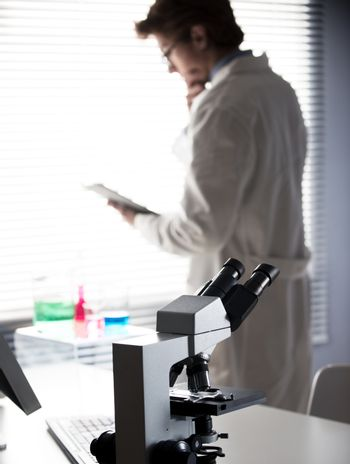 Researcher reading medical records in the chemical laboratory with microscope on foreground.