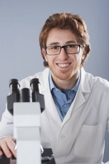 Student researcher using microscope and smiling at camera.