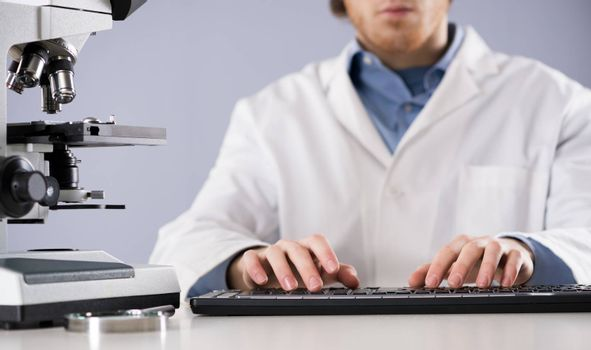 Researcher working at desk and typing on a keyboard, with microscope and magnifier.