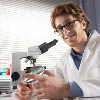 Chemical laboratory technician smiling and holding a magnifier with equipment on background.