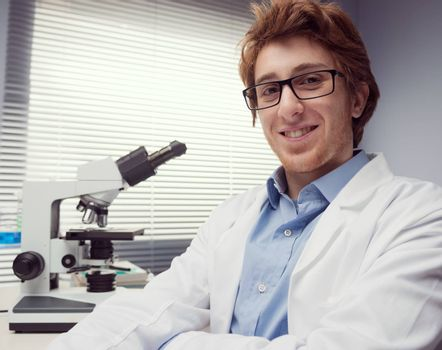 Student researcher smiling with arms crossed and microscope on background.