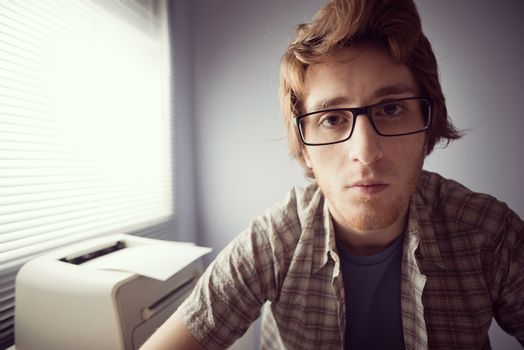 Young nerd guy staring at monitor with pensive expression.