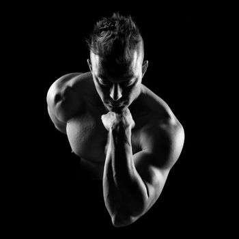 Body builder posing and showing bicep muscle on dark background.