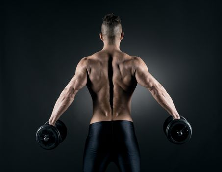 Muscular attractive man weightlifting on dark background.