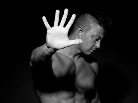 Muscular man hiding with hand raised on black background.
