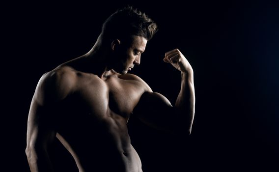 Body builder posing and showing off bicep muscle on dark background.