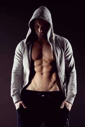 Body builder in hooded shirt with bare chest.