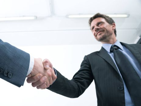 Confident businessmen shaking hands with empty white room on background.