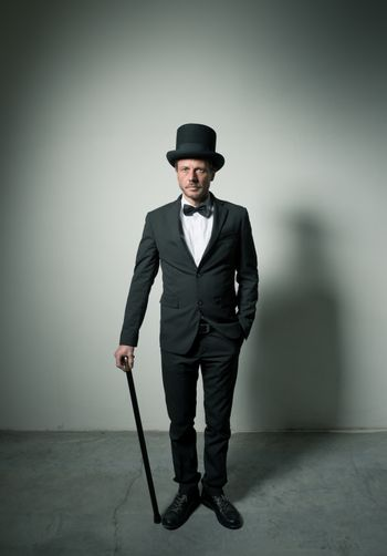 Classy gentleman with bowler hat and cane looking confidently at camera.