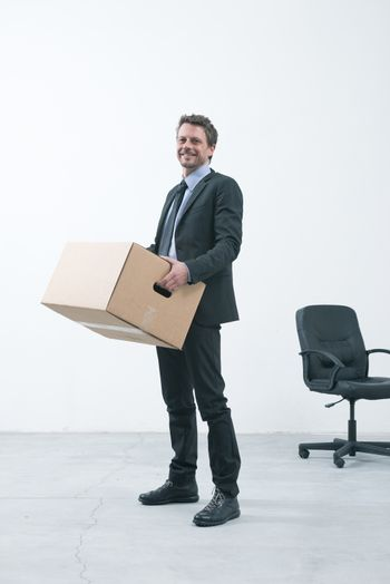 Smiling businessman holding a cardboard box and standing in an empty new office.
