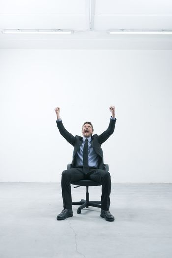 Joyful businessman with raised fists sitting on an office chair in his empty new office.