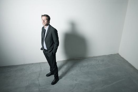 Attractive businessman standing with hands in pockets in an empty room with dramatic lighting.