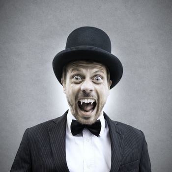 Scary vampire businessman screaming and showing fangs in vintage elegant outfit.
