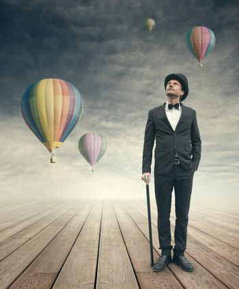 Attractive elegant businessman looking up at hot air balloons in the sky.