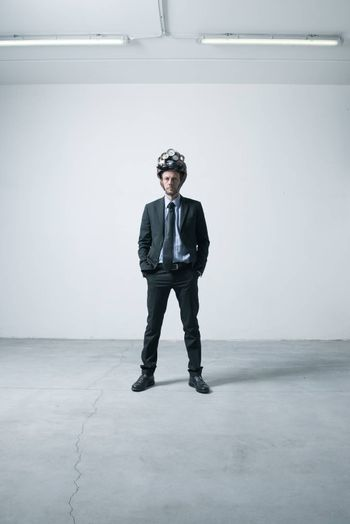 Confident businessman standing in an empty room with futuristic helmet.