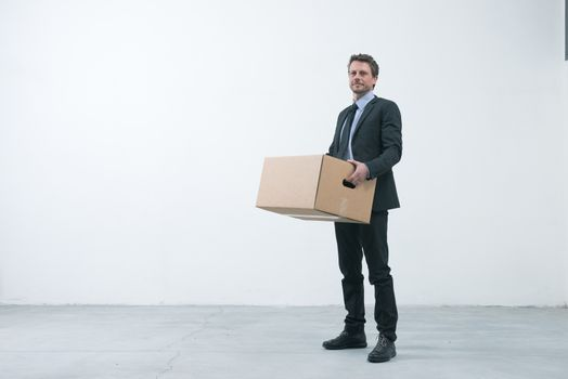 Smiling businessman holding a cardboard box and standing into an empty new office.