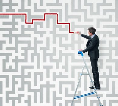 Elegant businessman on a ladder solving a maze with a brush.
