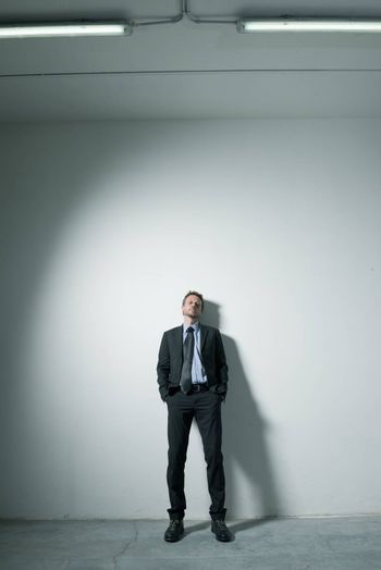 Attractive businessman leaning on a wall with hands in pockets and dramatic lighting.