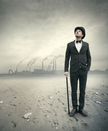Vintage businessman looking away with polluting factory and post atomic landscape on background.