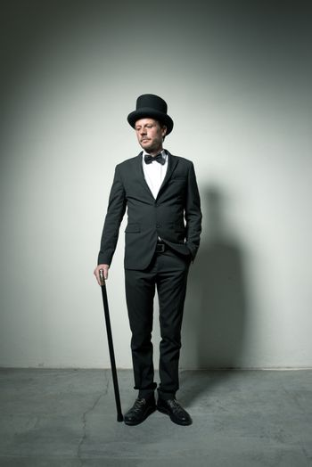 Classy gentleman with bowler hat and cane looking down