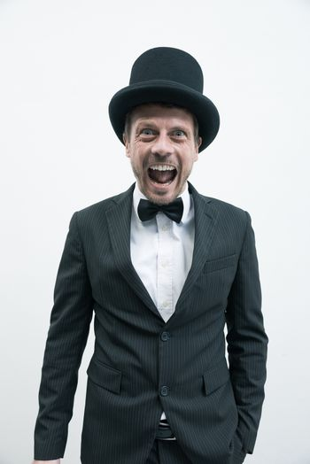 Vintage gentleman with bowler hat and bow tie screaming at camera.