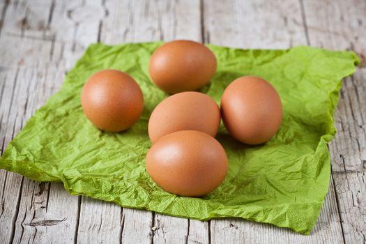 fresh brown eggs on green napkin