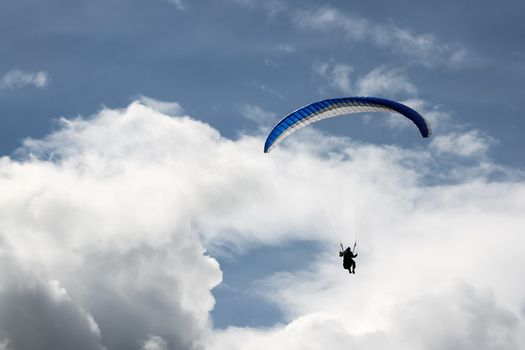 Paragliding in the blue cloudy skies